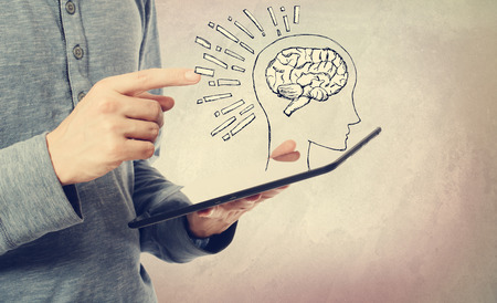 Brain illustration with man holding a tablet computer Imagens