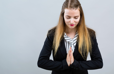 Young woman bowing with hands together on a gray background 스톡 콘텐츠 - 115462538