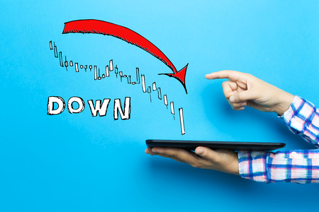 Market down trend chart with a tablet computer on a blue background Stock Photo