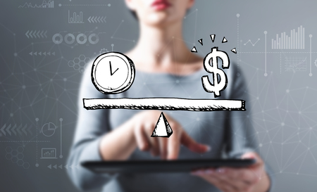Time and money on the scale with business woman using a tablet computer
