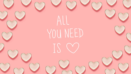 All You Need Is Love message with many heart dishes on a pink background