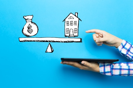 House and money on the scale with a tablet computer on a blue background
