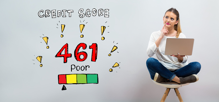 Poor credit score theme with young woman using her laptop on a grey background