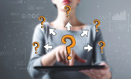 Big and small question marks with arrows with business woman using a tablet computer Imagens