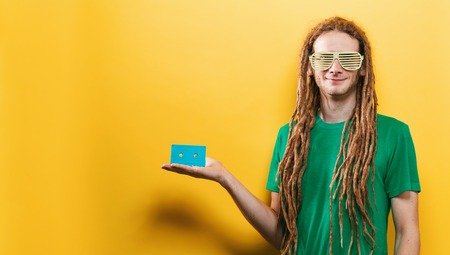 Happy man holding a retro cassette tape on a yellow background