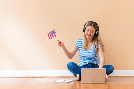 Mujer joven con bandera de Estados Unidos usando una computadora portátil contra una gran pared interior Foto de archivo