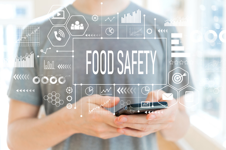 Food safety with young man using a smartphone Foto de archivo