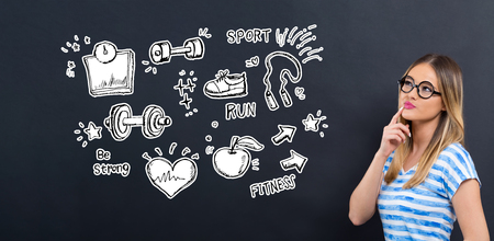 Fitness and diet with young woman in front of a blackboard