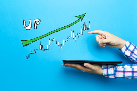 Market up trend chart with a tablet computer on a blue background 版權商用圖片