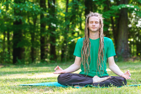 Man in a meditation pose outside in a field surrounded by forest