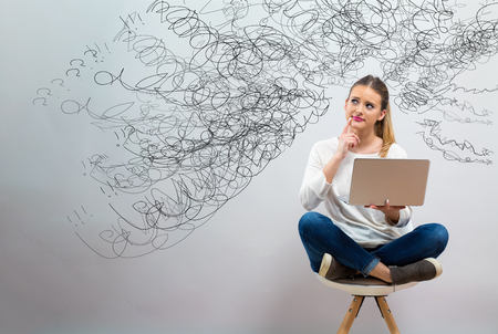 Confused concept with young woman using her laptop on a grey background Foto de archivo - 115932323