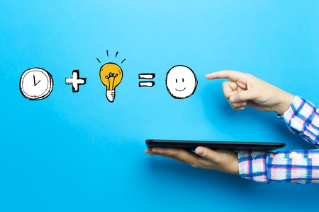 Time plus idea equals happy with a tablet computer on a blue background