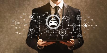 EV with businessman holding a tablet computer on a dark vintage background