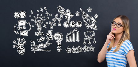 Business strategy ideas with young woman in front of a blackboard