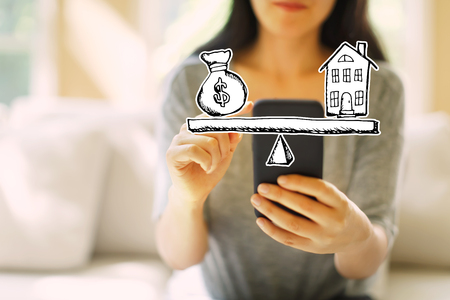 House and money on the scale with woman using her smartphone in a living room Stock Photo
