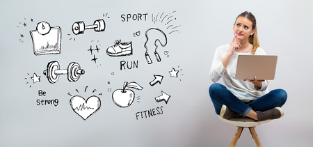 Fitness and diet with young woman using her laptop on a grey background Standard-Bild - 116438570