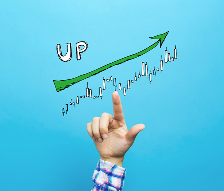 Market up trend chart with hand on a blue background 免版税图像