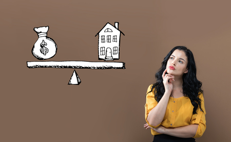 House and money on the scale with young businesswoman on a brown background