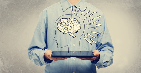 Brain illustration with young man holding a tablet computer Stock Photo