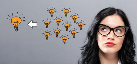 Many small ideas into one big idea with young businesswoman in a thoughtful face