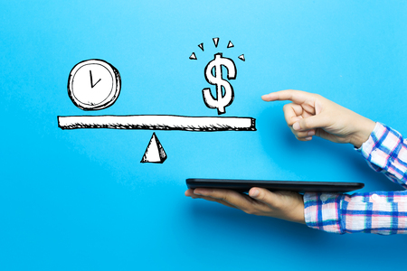 Time and money on the scale with a tablet computer on a blue background Stock fotó