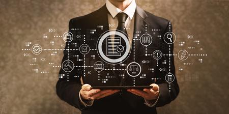Tema de cumplimiento con el empresario sosteniendo una tableta sobre un fondo oscuro de la vendimia