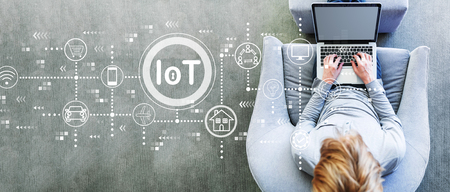 IoT theme with man using a laptop in a modern gray chair 写真素材