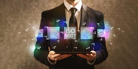 ISO 9001 with businessman holding a tablet computer on a dark vintage background Standard-Bild - 116652410