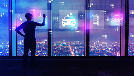 EV with man writing on large windows high above a sprawling city at night Standard-Bild - 116652416