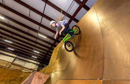 Man jumping and riding on a BMX bicycle at an extreme sports park Standard-Bild - 116652577