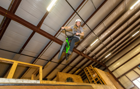 Man jumping and riding on a BMX bicycle at an extreme sports park Фото со стока