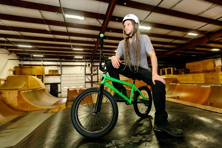 Portrait of a man with dredlocks and a helmet on a BMX bike at an extreme sports park Standard-Bild - 116652579