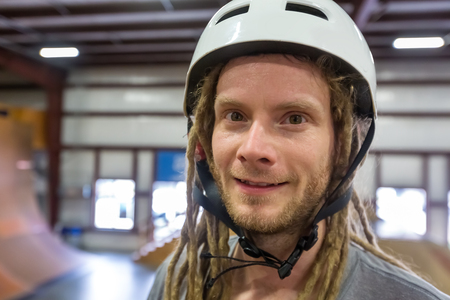 Portrait of a man with dredlocks and a helmet at an extreme sports park Stock Photo