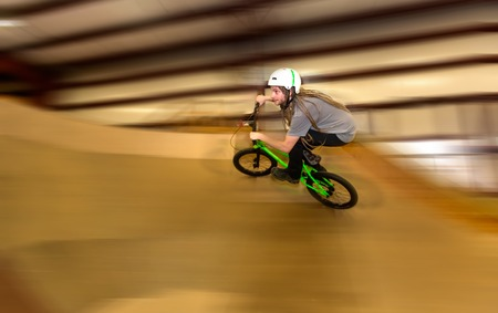 Man jumping and riding on a BMX bicycle at an extreme sports park Standard-Bild - 116691649