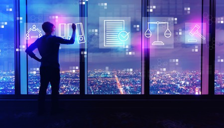 Compliance theme with man writing on large windows high above a sprawling city at night Standard-Bild - 116701398