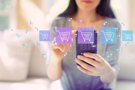 Thème d'achat en ligne avec une femme utilisant son smartphone dans un salon Banque d'images