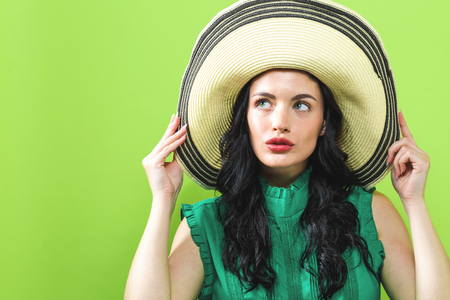 Young woman with a summer hat on a green background Stock Photo