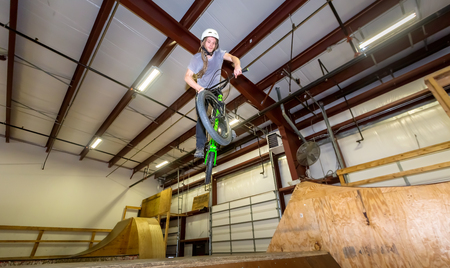 Man jumping and riding on a BMX bicycle at an extreme sports park Imagens
