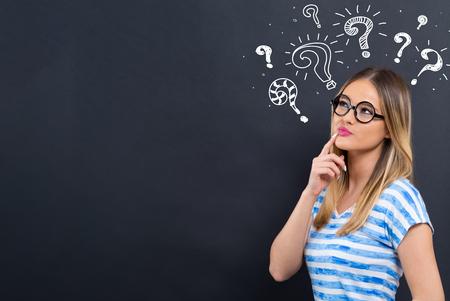 Vraagtekens met jonge vrouw voor een schoolbord