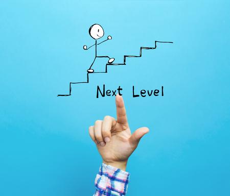 Concepto de siguiente nivel con la mano sobre un fondo azul.