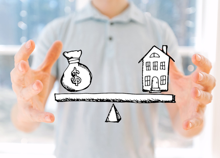 House and money on the scale with young man holding his hands