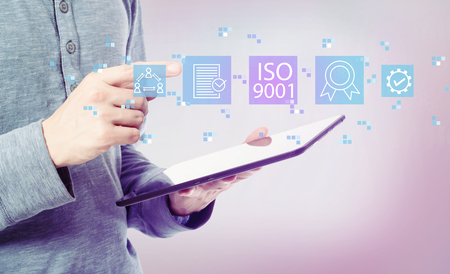 ISO 9001 with man holding a tablet computer Archivio Fotografico - 117360583