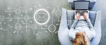 E-maile z mężczyzną korzystającym z laptopa w nowoczesnym szarym krześle