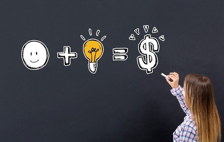 Gute Idee ist gleich Geld mit einer jungen Frau, die auf eine Tafel schreibt