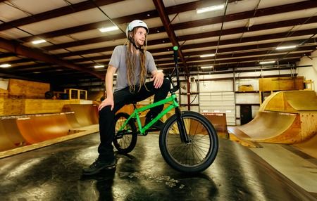 Portrait of a man with dredlocks and a helmet on a BMX bike at an extreme sports park 版權商用圖片