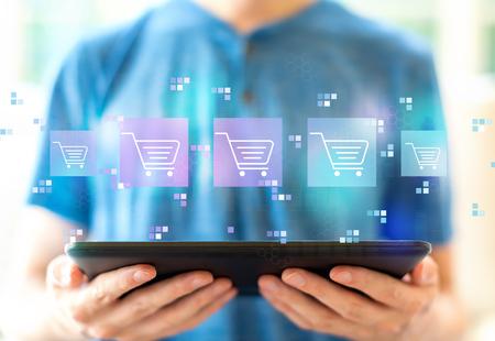 Online winkelthema met jonge man die een tabletcomputer gebruikt