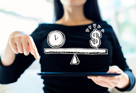 Time and money on the scale with woman using her tablet