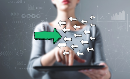 Arrow facing in a opposite direction with business woman using a tablet computer
