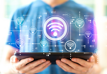 Wifi concept with young man using a tablet computer