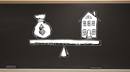 House and money on the scale on a blackboard with erasers